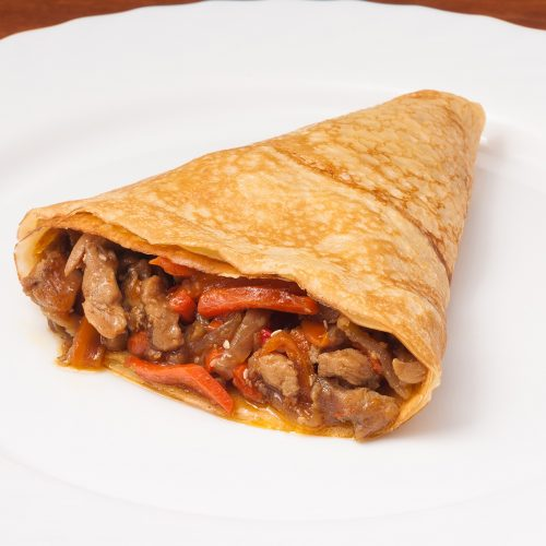 crepes with chicken and vegetables on a white plate